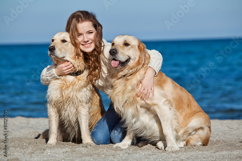 Photo woman are playing whit two dogs on the beach