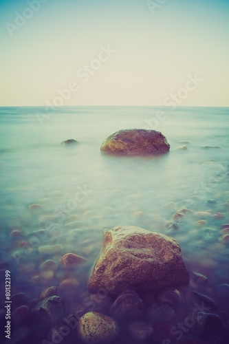 Poster Turquoise Vintage photo of rocky sea shore at sunset
