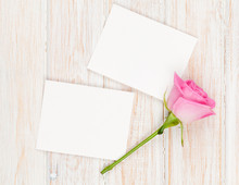 Blank Photo Frames And Pink Rose Over Wooden Table