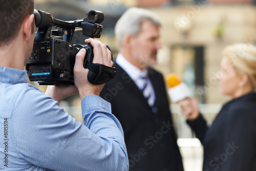Obraz na plátne Cameraman Recording Female Journalist Interviewing Businessman