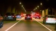 Many cars make jam in dark tunnel with illumination, view from car in motion