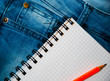 notebook and pencil on jeans background