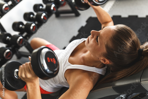 Fotografiet  Woman lifting  weights and working on her chest at the  gym