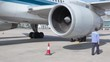Worker checks turbine of aircraft which stands at airport field