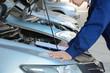 Auto mechanic checking car engine