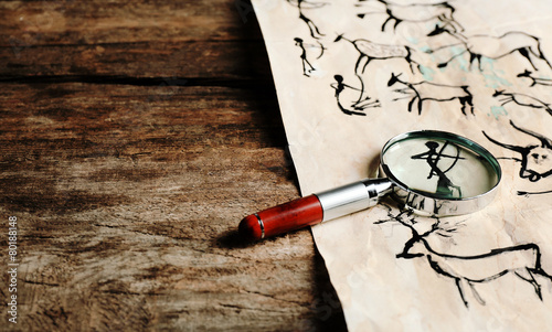 Photo Rock paintings with magnifier on paper on wooden table close up