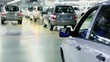 Cars comes and rides backward in hangar of factory, (unfocused)