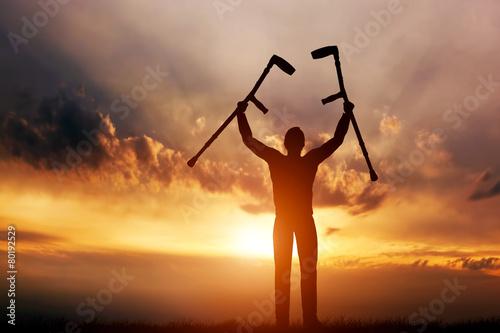Foto Ein behinderter Mann, der seine Krücken bei Sonnenuntergang zu erhöhen