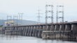 Trucks ride by dam of Hydroelectric power station on river