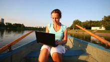 Woman Sits In Small Boat And Looks At Laptop On Pond