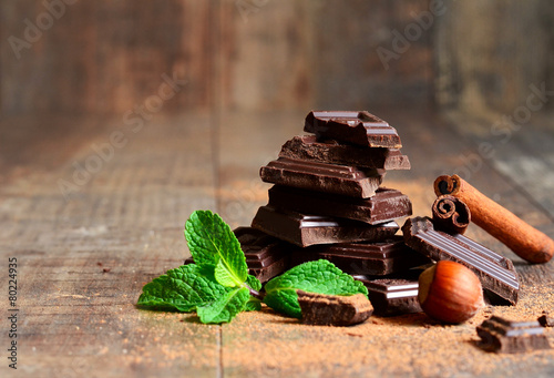 Fotografie, Obraz  Stack of chocolate slices with mint leaf,hazelnut and cinnamon.