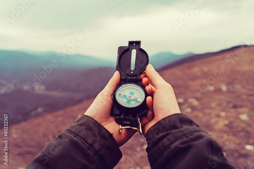 Obraz Hiker woman with a compass in the mountains - fototapety do salonu