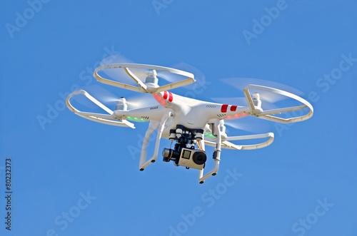 Fototapeta white drone hovering in blue sky obraz