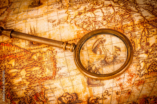 In de dag Retro Vintage magnifying glass lies on an ancient world map