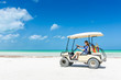 Young woman driving golf cart along tropical sandy beach