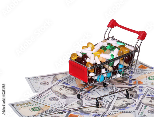 Poster Shopping cart full with pills over dollar bills, isolated