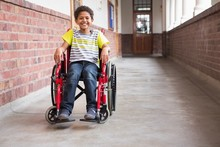 Cute Disabled Mixed Race Pupil Smiling At Camera In Hall