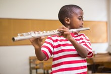 Cute Pupil Playing Flute In Classroom