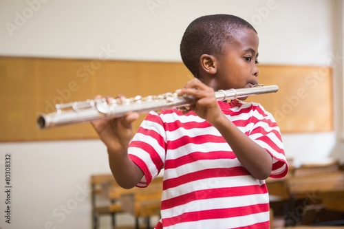 Foto Cute pupil playing flute in classroom