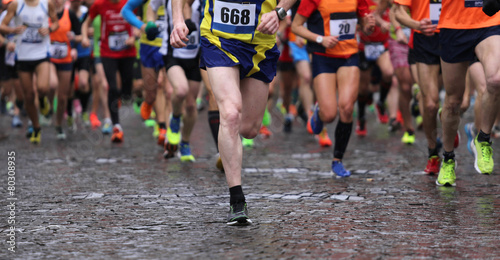 Fotografía  runners during marathon while it is raining