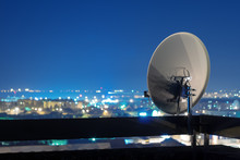 Satellite Dish Antenna On Rooftop At Night