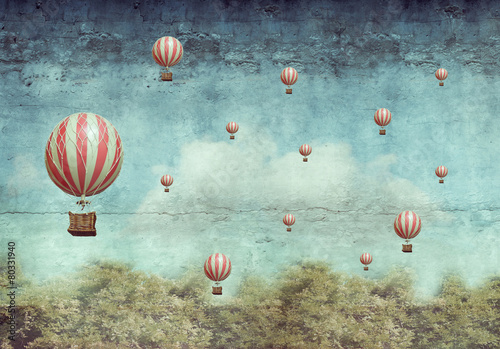 Hot air ballons flying over a forest