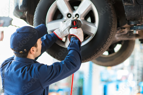 Fototapeta Mechanician changing car wheel in auto repair shop obraz