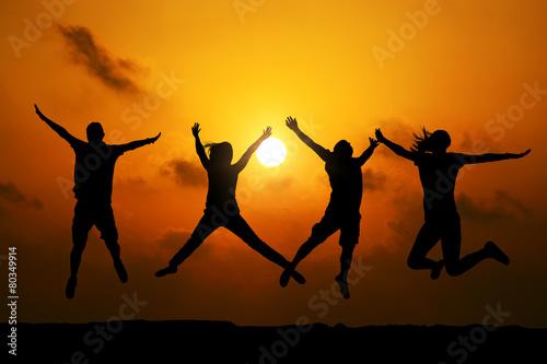 Fotografia  Four friends jumping  at sunset