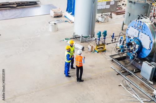 Fototapeta Worker and engineer discussing at machine obraz