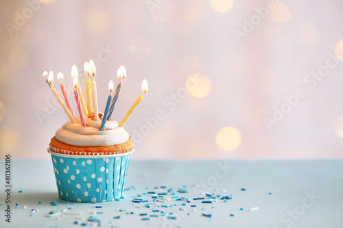 Delicious birthday cupcake on table on light background Poster