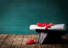 Academic. A Diploma Scroll Tied With Red Ribbon, Resting On A