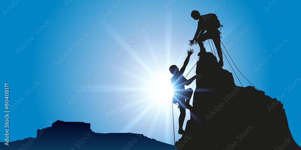 Fototapeta Concept de la solidarité, avec deux alpinistes qui arrivent au sommet d'une montagne après l'avoir escaladé avec succès.