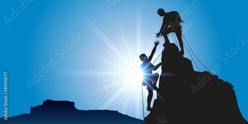 Fototapeta Concept de la solidarité, avec deux alpinistes qui arrivent au sommet d'une montagne après l'avoir escaladé avec succès