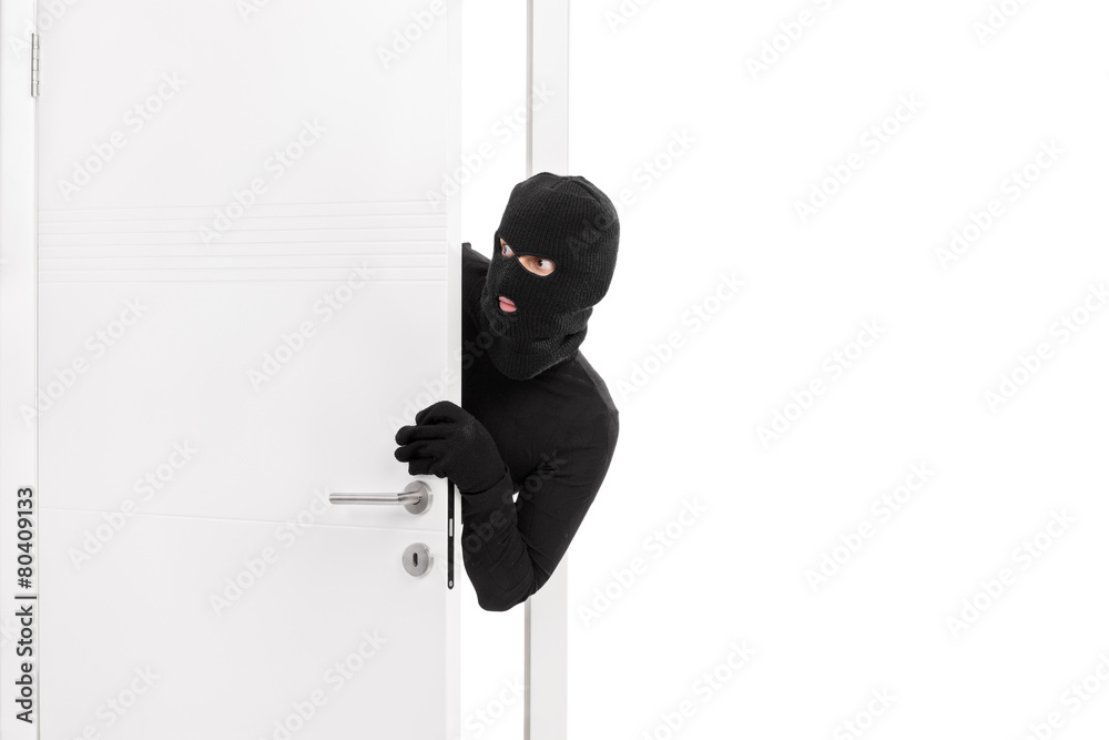 Fototapeta Thief breaking into a room and carefully looking around