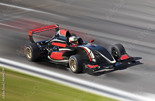 Fotografia, Obraz  F1 race car racing on a track with motion blur