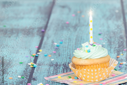 фотография  Pastel cupcake with a candle on vintage background