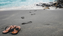 Human Leave His Flip Flops On The Black Sandy Beach And Go To Sw