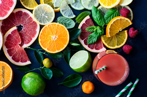 Fresh citrus slices and juice on black background top view
