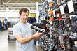 Man chooses roller skates in sports shop