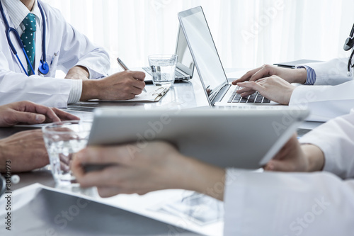 Photo Four doctors are conference in medical office