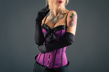 Portrait Of A Busty Woman Wearing Purple Vintage Corset And Blac