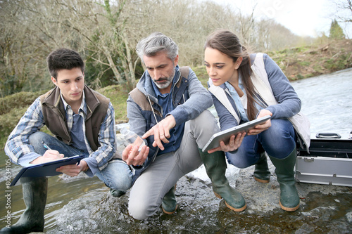 Fotografie, Obraz  Biologist with students in science testing river water