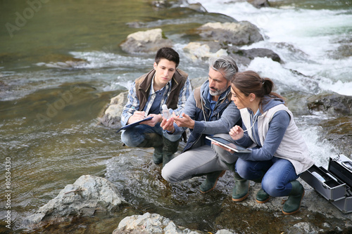 Fotografía  Biologist with students in science testing river water
