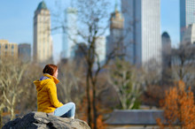 Young Woman Looking At Skyscrapers In Central Park