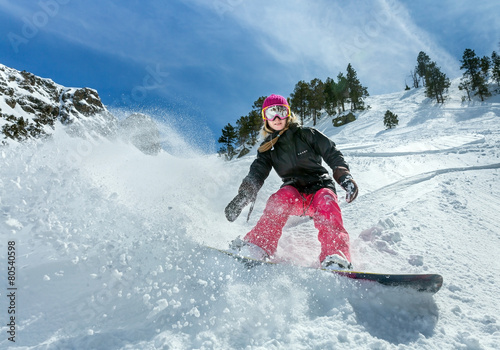 Poster Glisse hiver Woman snowboarder in motion in mountains
