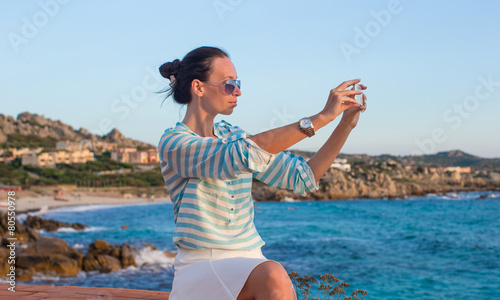 Fototapety, obrazy: Young woman with her phone during summer vacation