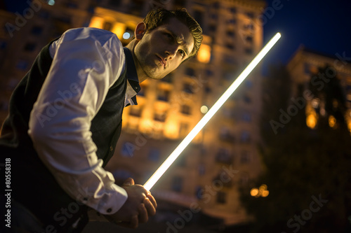 Photo  Handsome guy holding a lightsaber Jedi