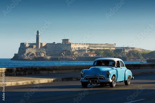 In de dag Havana Old classic car on street of Havana with ocean and lighthouse in