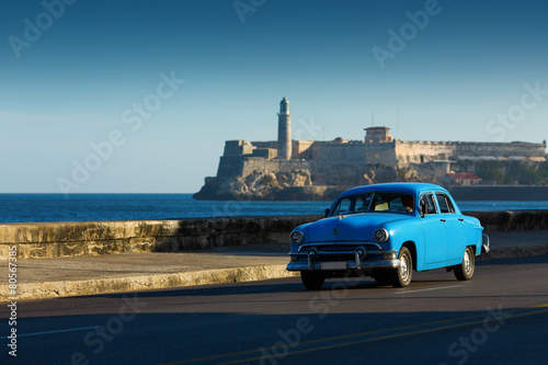 Poster Havana Old classic car on street of Havana with ocean and lighthouse in
