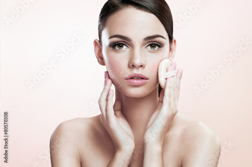 Young lady applying blusher on her face with powder puff Wallpaper Mural